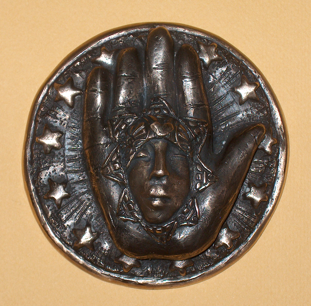 cast bronze medal with hand face and stars